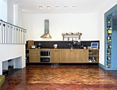 Herring-bone parquet in an open-plan kitchen with a counter unit and a gallery with white balustrade