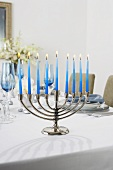 Manora with Lit Blue Candles on a Dining Table Set for Hanukkah