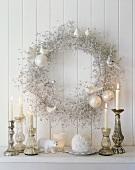 Weihnachtsdekoration mit Kerzen und Kranz an der Wand