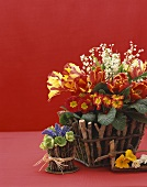 Two Flower Arrangements in Stick Baskets, On a Red Background