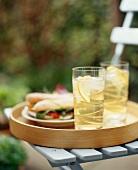 Tablett mit Eistee und Sandwiches auf Gartenstuhl im Freien
