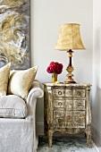 Kleine Antikkommode mit starker Patina, elegante Tischleuchte und rotes Blumensträusschen