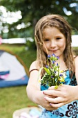 Young Girl Holding a Bouquet of Wildflowers; Campsite