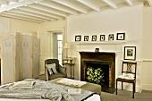 Klassisch elegantes Schlafzimmer mit altem Kamin und weisser Holzbalkendecke