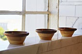 Three Wooden Bowls on Marble Ledge by Window