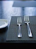 Zwei Gabeln auf Tischset