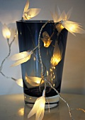 A vase decoarted with fairy lights