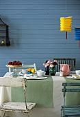 Gedeckter Frühlingstisch mit Kuchen, Tassen, Blumen im Freien