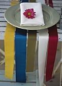 Wide ribbons as a place setting with a plate and a serviette