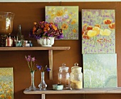 A wooden shelf with utensils and pictures of flowers by Nina Balthau