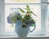 Hortensias and raspberry twigs in a jug on a windowsill