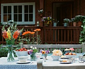 A table with flowers, strawberries, pastries and cups in the open air