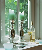 Candle holders and white wine on a window sill