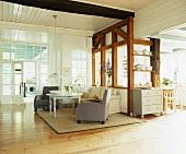Weitläufiger, offener Wohnraum mit Wohnzimmer im Stilmix, einem rustikalen Holzgerüst und dahinter angrenzendem Küchenbereich