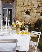A table laid outside with a bunch of flowers and fruit