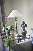 An antique table lamp with a white shade between a flower vase and an angel statue