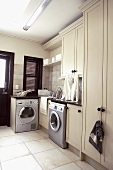 Stainless steel washing machines in a spacious, sand-coloured utility room