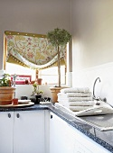 A kitchen window above a countertop drapped with fabric