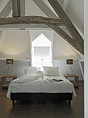 A white bedroom with a double bed in an attic with visible beams