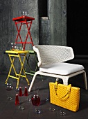 Glasses and vases arranged on and around a white wicker chair and a stack of coloured tables