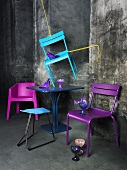 A chair hanging on a rope with a blue bistro table and purple plastic chairs underneath