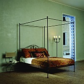 A green room with a black, steel-framed four-poster bed and oriental bed clothes