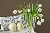 A display featuring white tulips in a glass vase, ostrich egg and a cushion