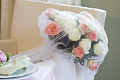 A wedding bouquet of white and pink roses wrapped in a veil