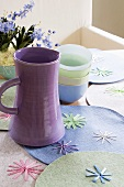 A purple water jug and a stack of bowls on place mats decorated with stars