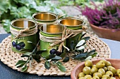 Decorated olive tins wiht twigs and a bowl of olives