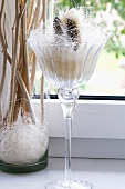 A stemmed glass filled with white straw with decoration