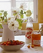 White flowers, a bowl of cherries and marmalade on a table