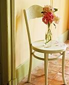 Blumenvase auf einem alten Holzstuhl