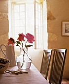A vase of roses on a kitchen table