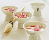 Pink rose petals in tea bowls with a calligraphy brush