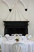Festively laid table with a white cloth in front of an open fire