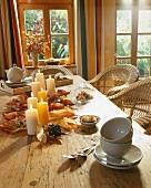 Holztisch mit Herbstdeko und Teegeschirr