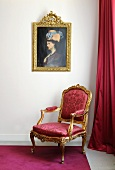 A baroque armchair with red upholstery underneath an oil painted in a gold frame