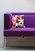 A purple sofa with arm and back rests and a colourful cushion in the corner