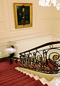 A flight of stairs in a manor house with red carpet runner
