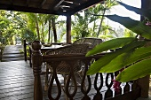 A seating area on a wooden terrace in tropical surroundings