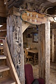 A view into a wooden hut with a rustic interior and antlers on a wooden beam