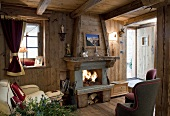 A cosy living room with a fireplace in a wooden hut