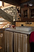 A stone wash basin in the kitchen corner of a rustic house