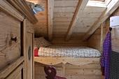 Eingebautes Bett unter dem Dach eines holzvertäfeltem Zimmer