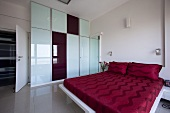 A large bedroom with a bed with red bed clothes