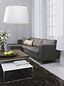 A sofa with a set of coffee tables and a white lamp shade in the corner of a living room