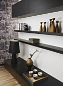 A stylish corner of a living room - black shelving on the floor and the wall