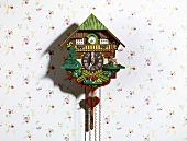 A cuckoo clock hanging on the wall with a roll mop fish in place of the cuckoo