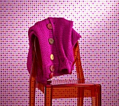 A pink cardigan with liquorice buttons on a red plastic chair